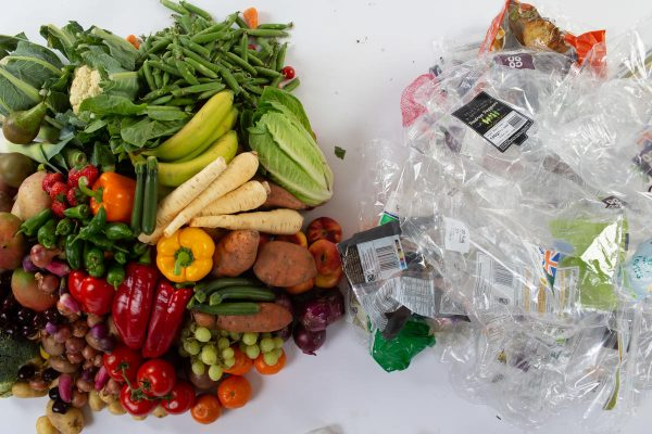 Plastic packaging next to fruit and vegetables.